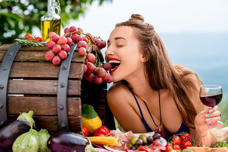 Photo for Beautiful woman tasting grapes lying on the grass with lots of tasty italian food and wine in the countryside in Tuscany. - Royalty Free Image