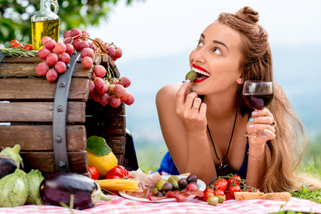 Photo for Beautiful woman tasting olive lying on the grass with lots of tasty italian food and wine in the countryside in Tuscany. - Royalty Free Image