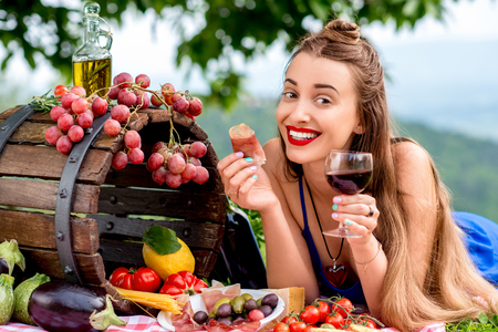 Photo for Beautiful woman tasting prosciutto lying on the grass with lots of tasty italian food and wine in the countryside in Tuscany. - Royalty Free Image