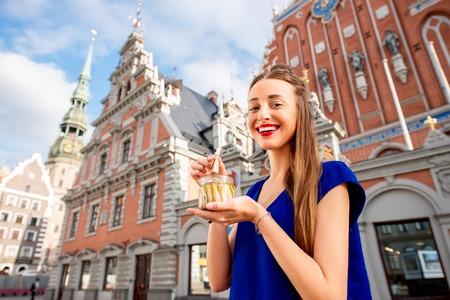 Photo pour Young woman eating Riga's sprats in the old town square in Latvia. Riga is famous for it's tasty golden and smoked fish called sprats. - image libre de droit