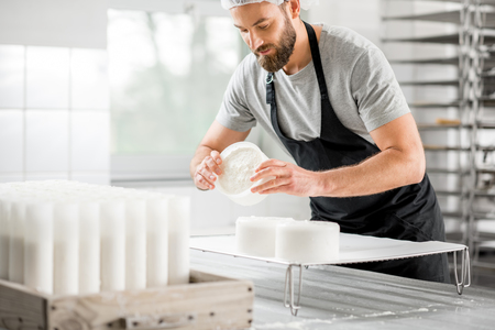 Photo pour Cheese maker at the manufacturing - image libre de droit