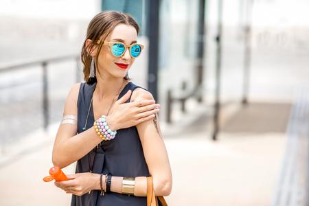 Photo pour Woman applying sunscreen lotion - image libre de droit