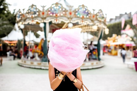 Photo for Woman with cotton candy at the amusement park - Royalty Free Image