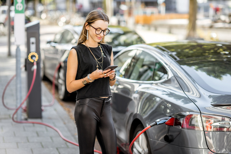 Foto de Woman charging electric car outdoors - Imagen libre de derechos