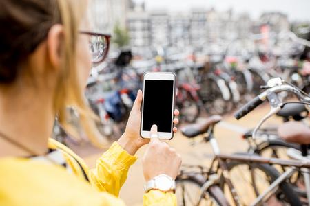 Photo pour Holding a phone on the bicycle parking background - image libre de droit