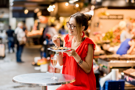 Photo pour Young woman in red dress having lunch with mussels and rose wine sitting at the food market - image libre de droit