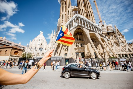 Foto de BARCELONA, SPAIN - August 16, 2017: Holding catalan flag in front of the famous Sagrada Familia Roman Catholic church in Barcelona, designed by architect Antoni Gaudi - Imagen libre de derechos