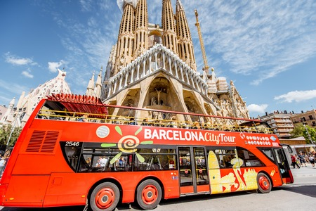 Foto de BARCELONA, SPAIN - August 16, 2017: Tourist bus near the famous Sagrada Familia roman catholic church in Barcelona, designed by catalan architect Antoni Gaudi - Imagen libre de derechos