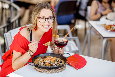 Foto de Young woman in red dress eating sea Paella, traditional Valencian rice dish, sitting outdoors at the restaurant in Valencia, Spain - Imagen libre de derechos