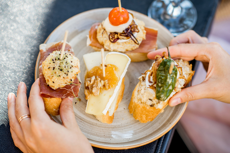 Photo pour Beautiful and colorful set of pinchos, traditional spanish snack related to tapas, outdoors on the table - image libre de droit
