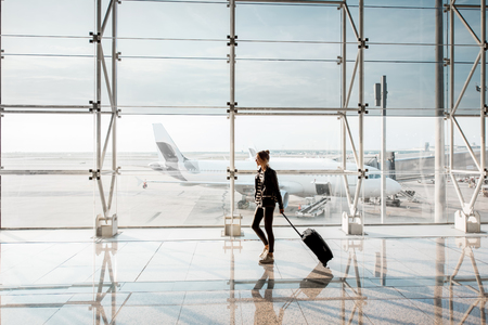 Photo pour View on the aiport window with woman walking with suitcase at the departure hall of the airport. Wide angle view with copy space - image libre de droit