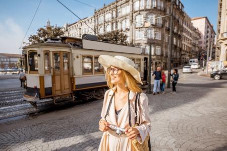 Foto de Lifestyle portrait of a woman with photo camera near the famous old touristic tram on the street in Porto city, Portugal - Imagen libre de derechos