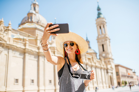 Photo for Young woman tourist making selfie photo in front of the famous cathedral on the central square during the sunny weather in Zaragoza city, Spain - Royalty Free Image