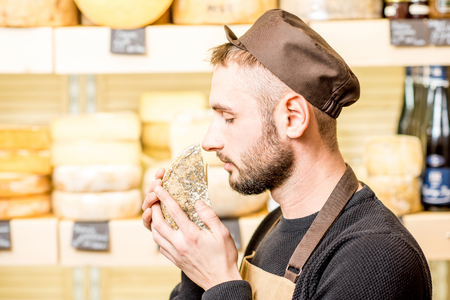 Foto de Portrait of a handsome cheese seller in uniform smelling seasoned cheese in front of the store showcase full of different cheeses - Imagen libre de derechos