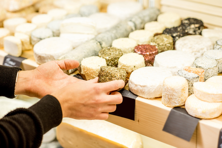 Photo pour Cheese seller putting goods on the shelves at the cheese store - image libre de droit