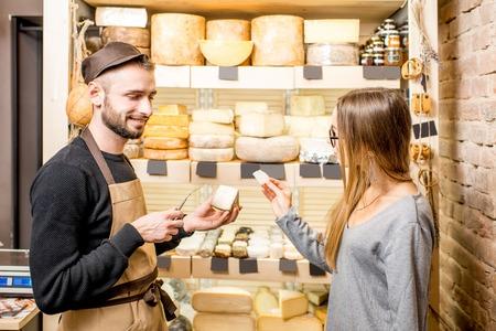 Foto de Salesman with a woman customer choosing a cheese for buying at the food store - Imagen libre de derechos