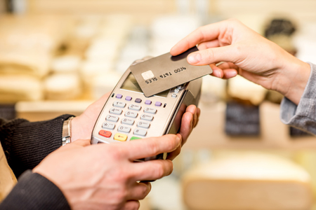 Photo for Woman paying with card contactless in the food store. Close-up view on the terminale and card - Royalty Free Image