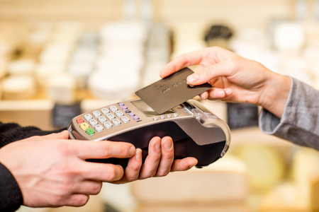 Photo pour Woman paying with card contactless in the food store. Close-up view on the terminale and card - image libre de droit