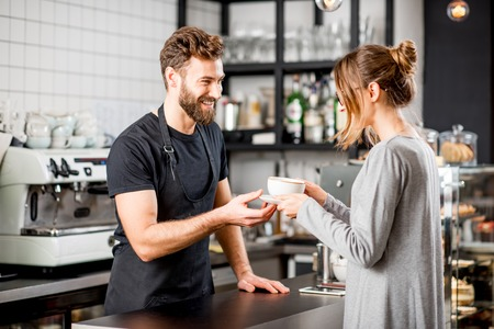 Photo for Handsome barista giving a coffee to the female client at the bar of the modern cafe - Royalty Free Image