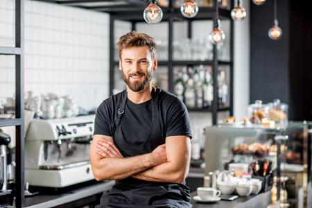 Foto de Portrait of a handsome barista in black t-shirt and apron sitting at the bar of the modern cafe - Imagen libre de derechos