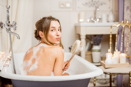 Photo pour Young playful woman washing with brush in the beautiful vintage bath full of foam in the bathroom decorated with candles - image libre de droit