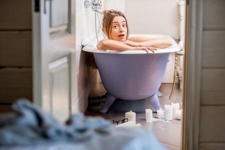Foto de Watching through the bathroom door on the surprised woman lying in the bathtub - Imagen libre de derechos
