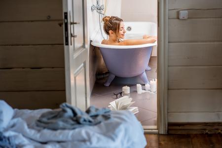 Foto de View through the bathroom door on the beautiful woman relaxing in the retro bathtub - Imagen libre de derechos