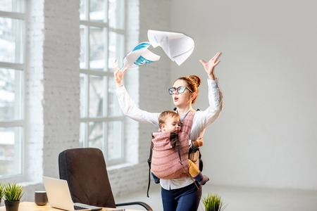 Foto de Multitasking and exhausted businesswoman throwing up a documents standing with her baby son during the work at the office - Imagen libre de derechos
