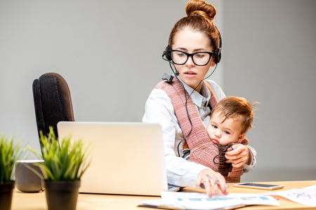 Photo for Multitasking businesswoman working with headset and laptop sitting with her baby son at the white office interior - Royalty Free Image
