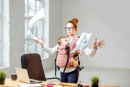 Photo pour Multitasking and exhausted businesswoman throwing up a documents standing with her baby son during the work at the office - image libre de droit