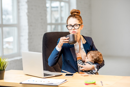 Foto de Young multitasking businessmam feeding her baby son with breast while having a break drinking coffee at the office - Imagen libre de derechos