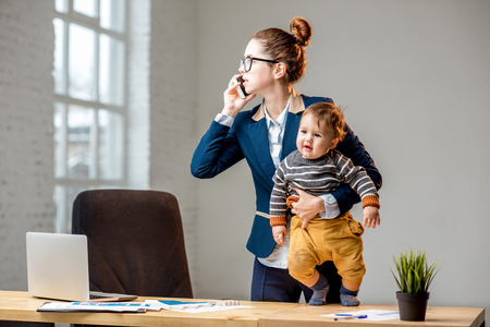 Photo pour Young multitasking businessmam dressed in the suit talking phone standing with her baby son at the office - image libre de droit