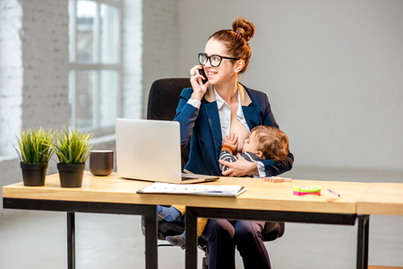Photo pour Young multitasking businessmam feeding her baby son with breast while working at the office - image libre de droit