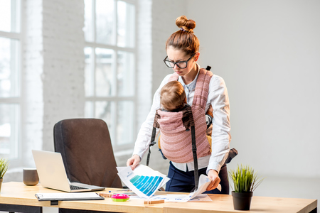 Foto de Exhausted businesswoman working with paper documents with her baby son at the office - Imagen libre de derechos