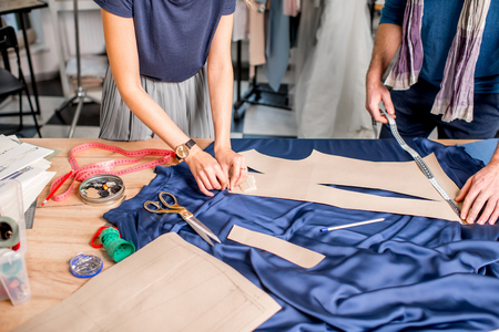 Foto de Cutting blue fabric on the table full of tailoring tools. Close-up view on the hands and fabric with no face - Imagen libre de derechos