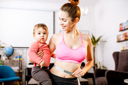 Photo for Young mother in sportswear measuring her waist worried about her weight after the child birth sitting with her baby son during the exercise - Royalty Free Image