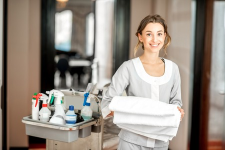 Photo pour Portrait of a young woman chambermaid holding a towel standing with maid cart full of cleaning stuff in the hotel corridor - image libre de droit