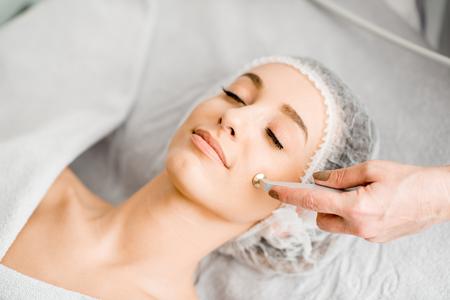 Foto de Young woman during the facial treatment procedure in the cosmetology office - Imagen libre de derechos