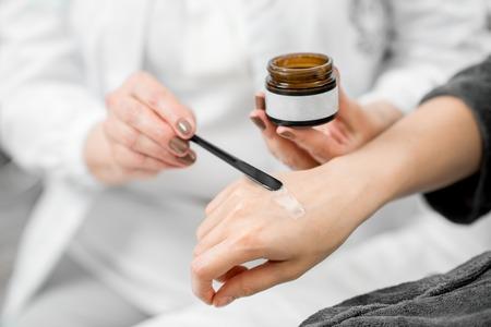 Foto de Doctor applying cream on the arm of the young client to try - Imagen libre de derechos
