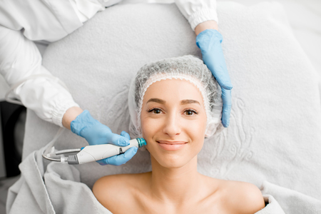 Photo for Young woman during the facial treatment procedure in the cosmetology office - Royalty Free Image