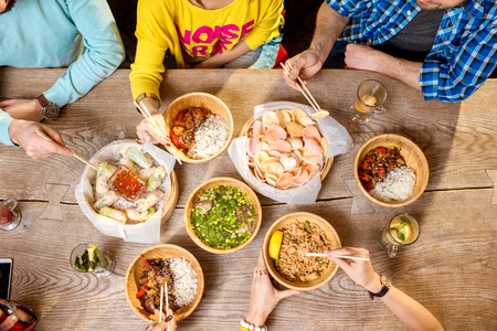 Foto de Top view on the table full of different asian meals served in the wooden plates and young people eating with sticks - Imagen libre de derechos