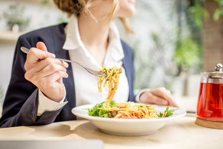 Photo for Businesswoman having lunch with pasta and fruit tea at the vegan restaurant on the green background - Royalty Free Image