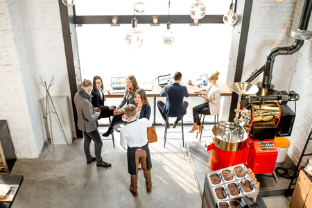 Foto de Top view on the cafe interior with business people having a conversation durnig a coffee time sitting with laptops near the window - Imagen libre de derechos