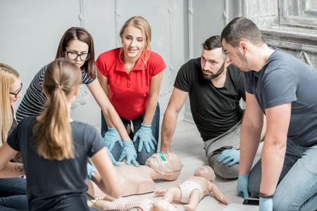 Foto de Group of people learning how to make first aid heart compressions with dummies during the training indoors - Imagen libre de derechos