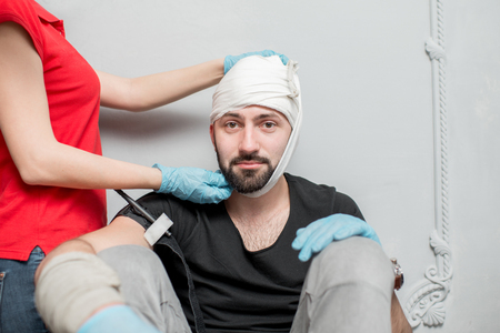 Photo for A group of people learning to apply bandage to prevent bleeding during the first aid training indoors - Royalty Free Image