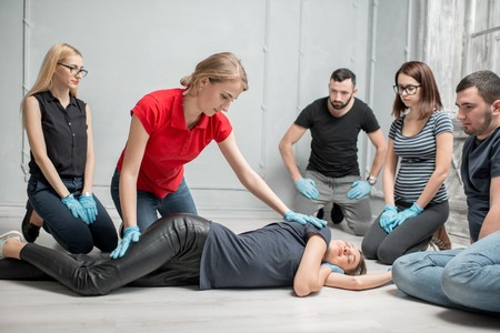 Photo for Young woman instructor showing how to lay down a woman during the first medical aid training indoors - Royalty Free Image