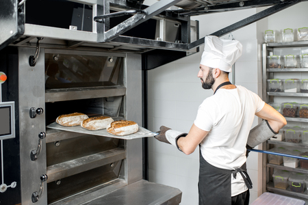 Photo for Baker taking off baked breads with shovel from the professional oven at the manufacturing - Royalty Free Image