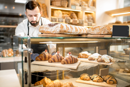 Photo for Seller putting delicious croissants on the store showcase of the bakery house - Royalty Free Image