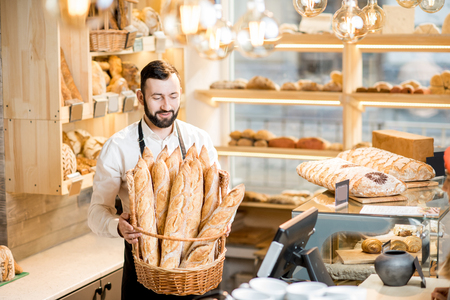 Photo for Handsome bread seller with basket full of baguettes in the beautiful store with bakery products - Royalty Free Image