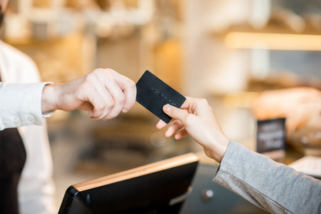 Photo for Paying by credit card in the store with bakery products. Close-up view on the hands and card - Royalty Free Image